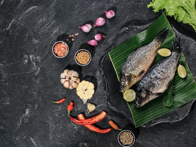 Rauwe ingrediënten van pesmol ikan mas gold fish met gele kerriekruiden