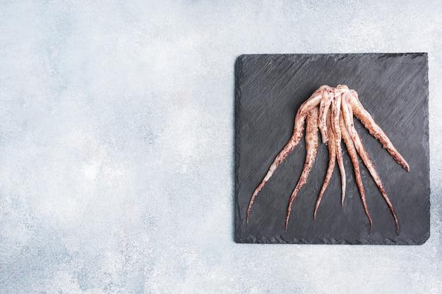 Rauwe inktvis tentakels op een bord van zwarte leisteen. kopieer ruimte bovenaanzicht. grijze achtergrond.