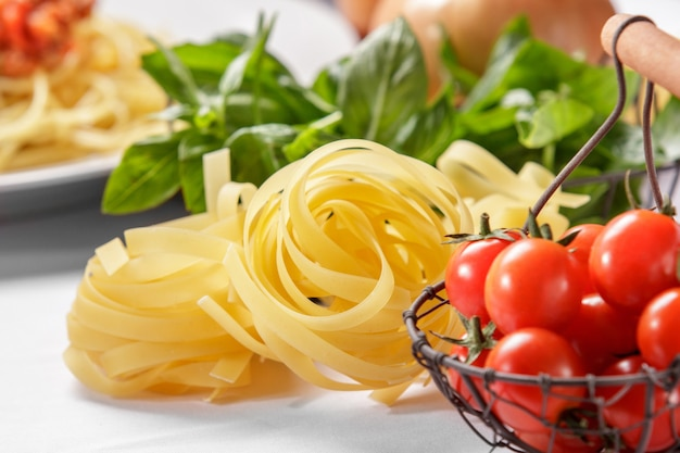 Rauwe italiaanse tagliatelle pasta en kerstomaatjes met basilicum op achtergrond
