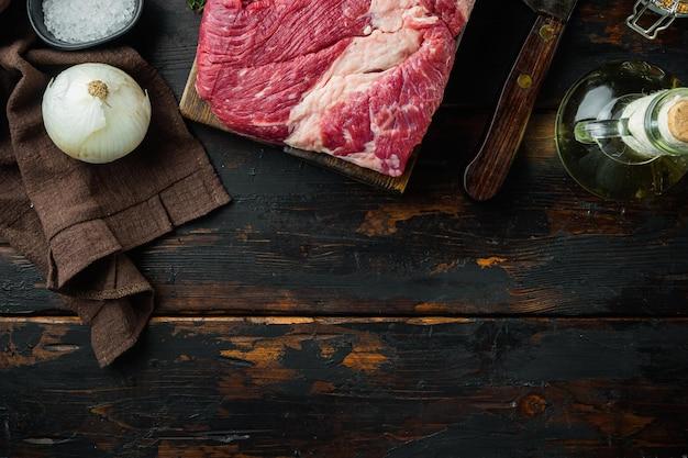 Rauwe kalfsborst rundvlees set, met ingrediënten voor het roken maken van barbecue, pastrami, genezen, op oude donkere houten tafel achtergrond, bovenaanzicht plat lag, met kopie ruimte voor tekst