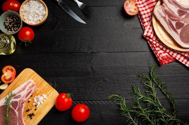 Rauwe karbonade steak op het donkere houten oppervlak.