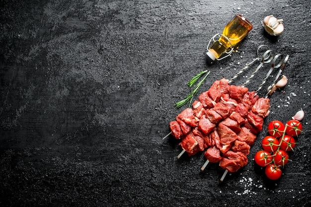 Rauwe kebab op spiesjes met tomaten, knoflook en olie in een fles op zwarte houten tafel