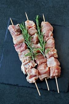Rauwe kebabs met rozemarijn en specerijen op een zwarte stenen bord.