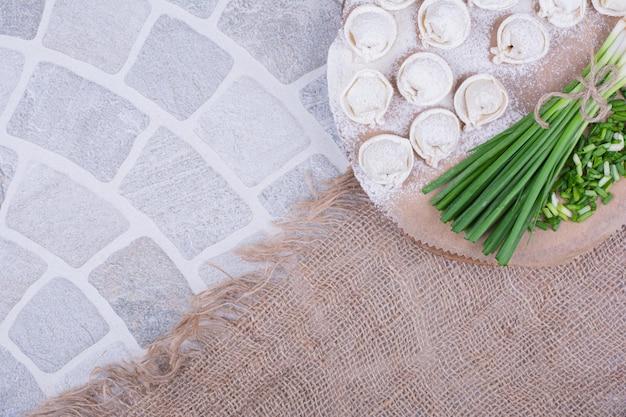 Rauwe khinkali-deeg op de bloem met een bosje groene ui. Gratis Foto