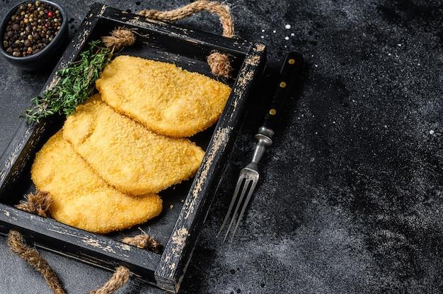 Rauwe kip cordon bleu vleeskoteletten in een houten bakje met kruiden