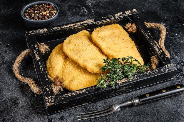 Rauwe kip cordon bleu vleeskoteletten in een houten dienblad met kruiden op houten tafel. bovenaanzicht.