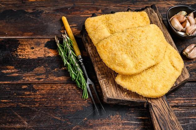 Rauwe kip cordon bleu vleeskoteletten met broodkruimels op een houten bord. donkere houten achtergrond. bovenaanzicht. ruimte kopiëren.