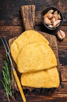 Rauwe kip cordon bleu vleeskoteletten met broodkruimels op een houten bord. donkere houten achtergrond. bovenaanzicht.