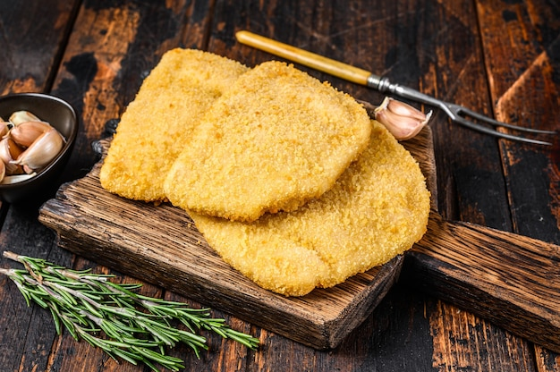 Rauwe kip cordon bleu vleeskoteletten met broodkruimels op een houten bord.
