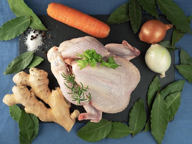 Rauwe kip met groenten op een zwarte stenen bord, gelegen op een blauwe tafellaken. bovenaanzicht. specerijen om te koken.