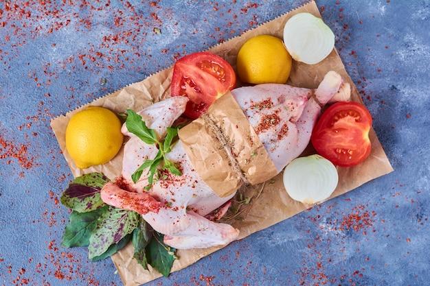 Rauwe kip met kruiden en specerijen op een houten bord op blauw