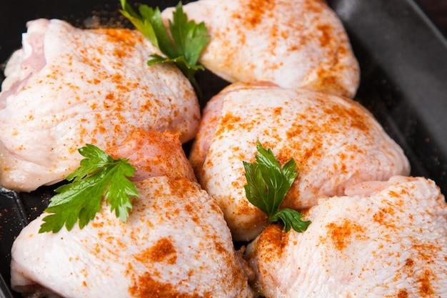 Rauwe kip met kruiden op koekenpan