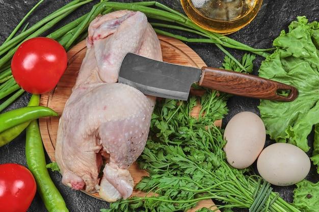 Rauwe kip op houten plaat met bos van verse groenten.