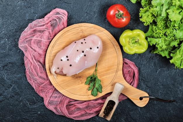 Rauwe kipfilet op een houten bord met groenten en tafellaken.
