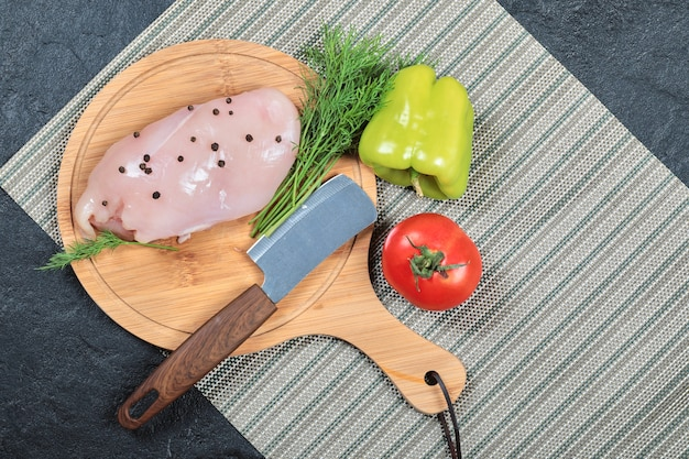 Rauwe kipfilet op een houten bord met paprika, mes en tomaat.