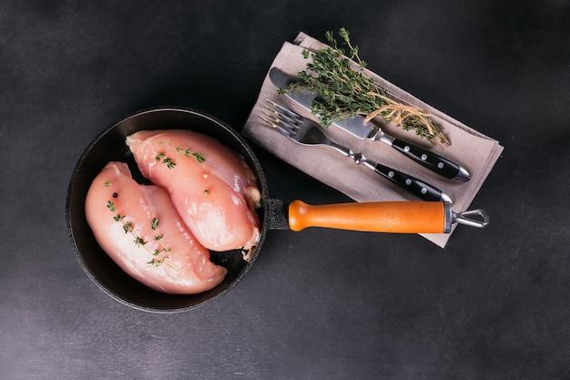 Rauwe kipfilets in zwarte pan met specerijen en kruiden. ingrediënten koken. natuurlijk gezond voedselconcept. bovenaanzicht met kopieerruimte