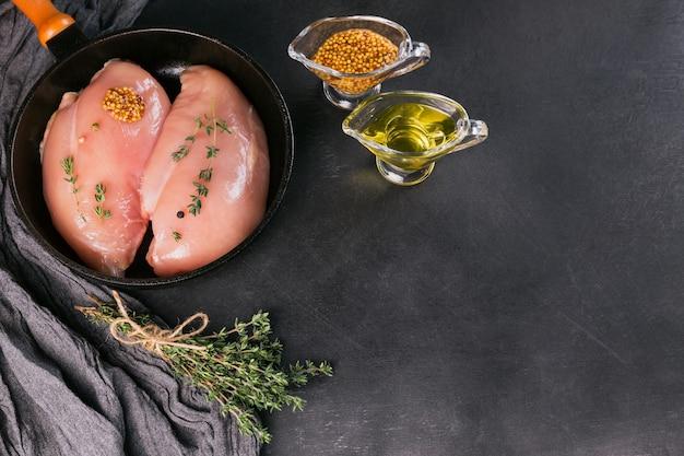 Rauwe kipfilets in zwarte pan met specerijen en kruiden. ingrediënten koken. natuurlijk gezond voedselconcept. platliggend met ruimte voor tekst