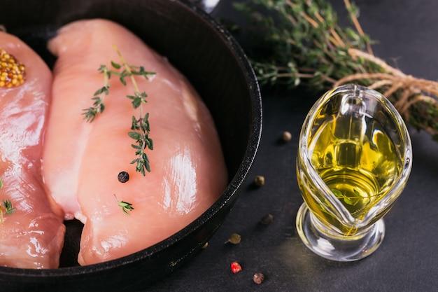 Rauwe kipfilets in zwarte pan met specerijen en kruiden. ingrediënten koken. natuurlijk gezond voedselconcept.