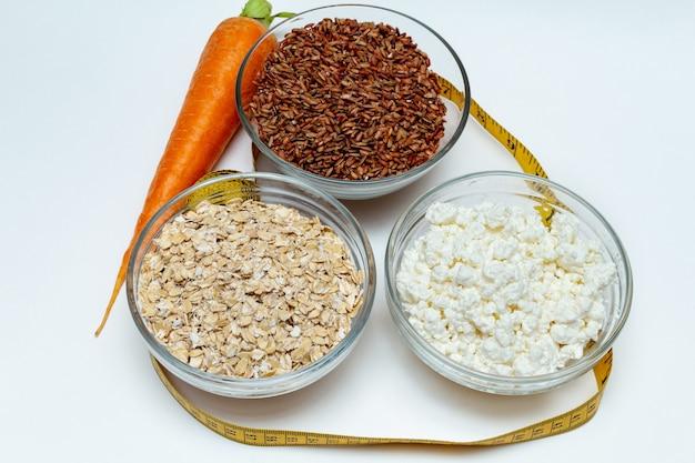 Rauwe kippenborst, granen, bruine rijst, meetlint, boerderij kwark wortel close-up op wit