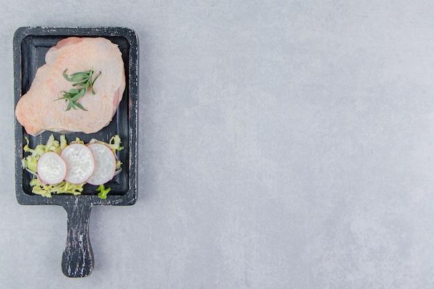 Rauwe kippenborsten en kruiden op het bord, op het witte oppervlak
