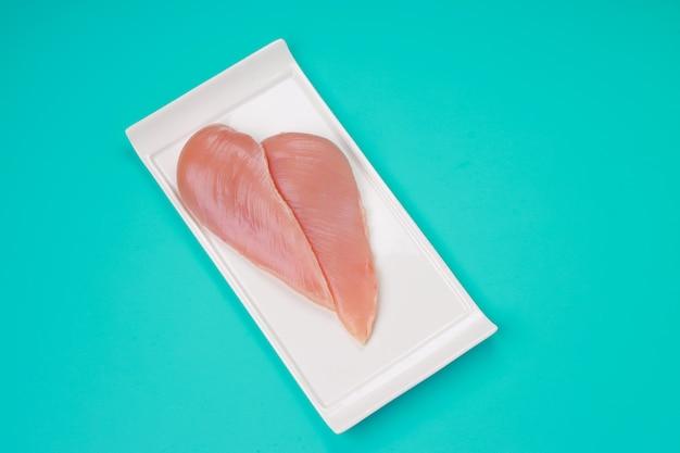 Rauwe kippenborstfilet zonder vel gerangschikt op een wit rechthoekig plat servies