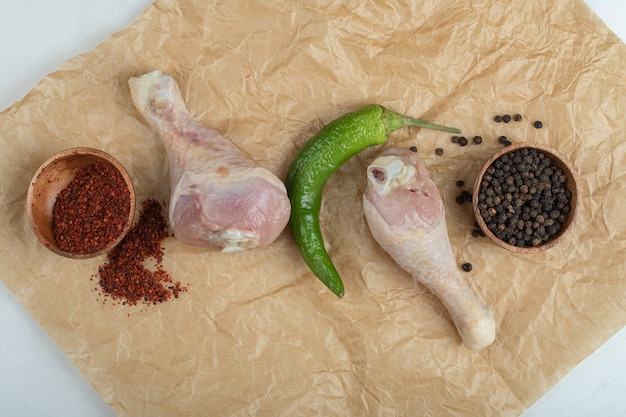 Rauwe kippenboutjes met kruiden. rode en zwarte paprika's.