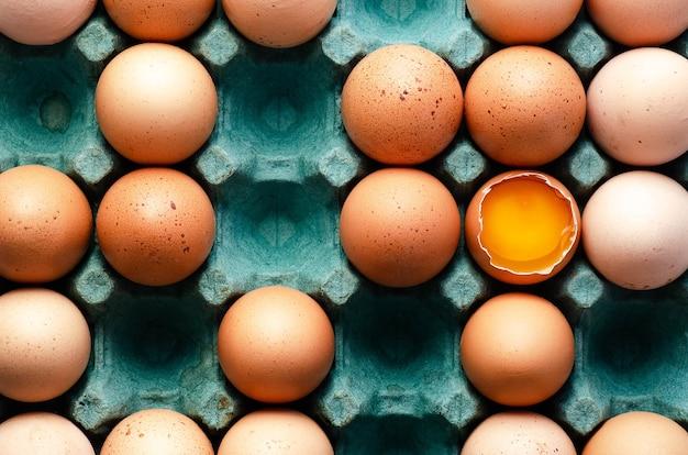 Rauwe kippeneieren in een turquoise eierdoos