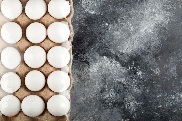 Rauwe kippeneieren in eierdoos op een marmeren oppervlak.