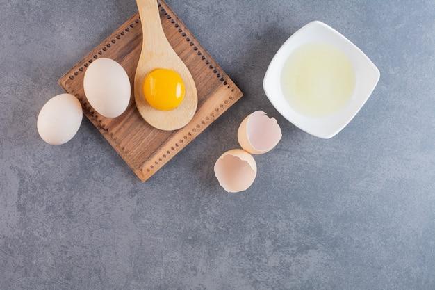 Rauwe kippeneieren met dooier en eiwit op stenen tafel.