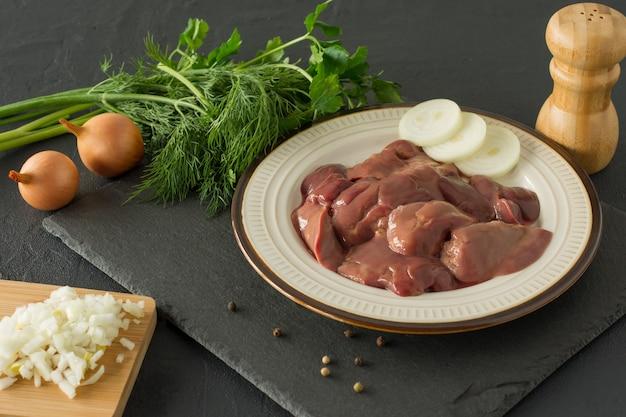 Rauwe kippenlever in kom op zwart ingrediënten voor het koken.