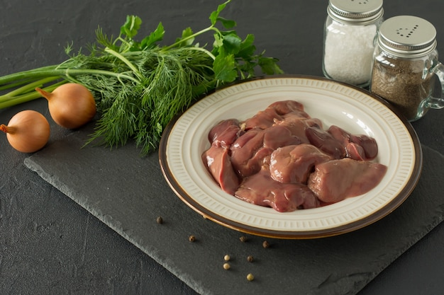Rauwe kippenlever in kom op zwarte achtergrond. ingrediënten voor het koken.