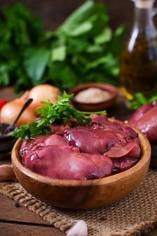 Rauwe kippenlever voor het koken met uien en paprika