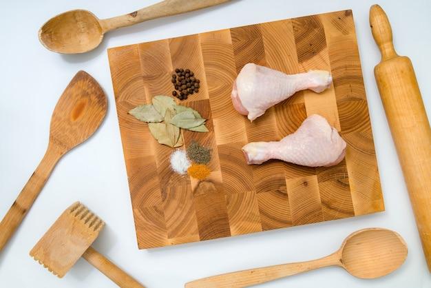 Rauwe kippenpoten en basiskruiden op handgemaakte houten plank in de keuken Premium Foto