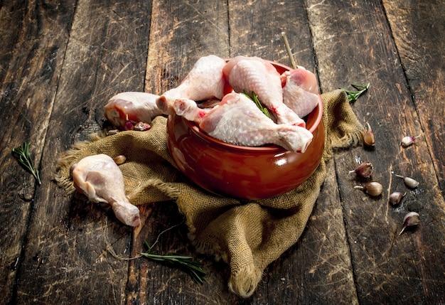 Rauwe kippenpoten met knoflook en kruiden in een kom. op houten achtergrond.