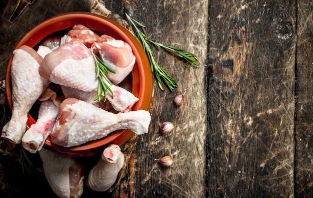 Rauwe kippenpoten met knoflook en kruiden in een kom op houten lijst.