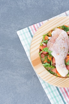 Rauwe kippentrommelstok en gesneden groenten op houten plaat.