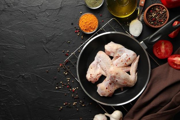Rauwe kippenvlees en specerijen op zwarte ruimte, bovenaanzicht. kip koken