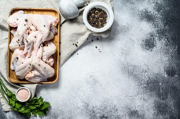 Rauwe kippenvleugels. biologisch pluimvee. bovenaanzicht. grijze achtergrond. ruimte voor tekst