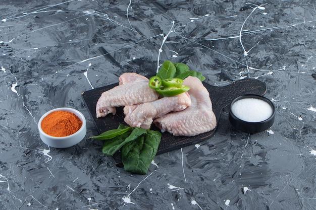 Rauwe kippenvleugels en spinazie op een snijplank naast kruiden- en zoutkom, op het marmeren oppervlak.