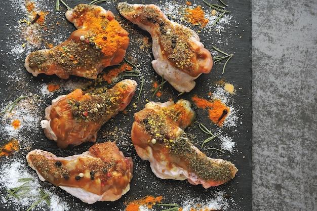 Rauwe kippenvleugels gemarineerd in kruiden op een zwarte stenen bord.