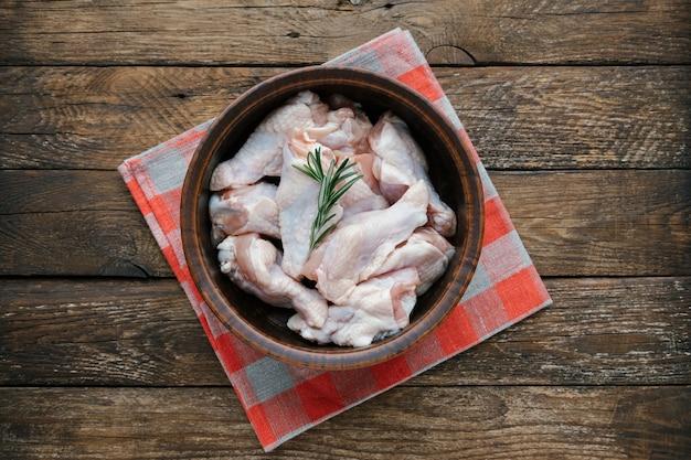 Rauwe kippenvleugels in de kom bereiden voor het koken van verse ongekookte drumette of drumstick met rozemarijn...