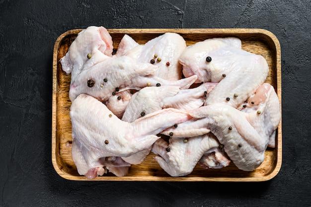 Rauwe kippenvleugels in een houten kom. biologisch vlees van de boerderij. bovenaanzicht. zwarte achtergrond