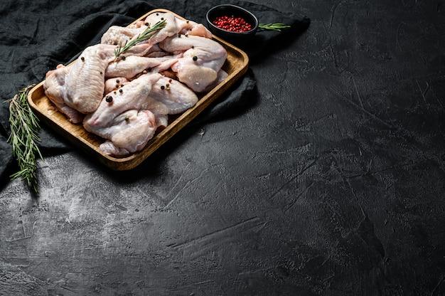 Rauwe kippenvleugels in een houten kom. biologisch vlees van de boerderij. bovenaanzicht. zwarte muur. ruimte voor tekst.