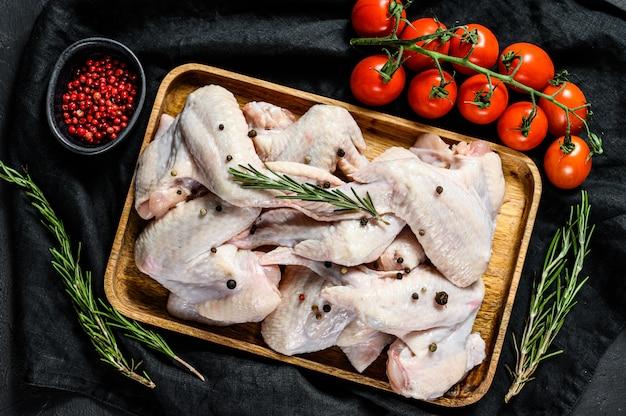 Rauwe kippenvleugels in een houten kom, koken ingrediënten rozemarijn en roze peper. biologisch vlees van de boerderij. bovenaanzicht. zwarte achtergrond