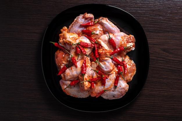 Rauwe kippenvleugels in een marinade met kruiden op een zwarte plaat