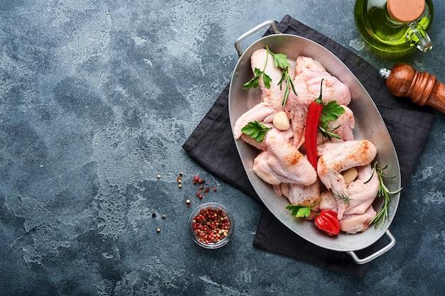 Rauwe kippenvleugels in metalen pan of kom met kruiden en ingrediënten voor het koken op donkergrijze leisteen, steen of betonnen ondergrond. rauw vlees met kruiden aan zwarte tafel. bovenaanzicht. bespotten.