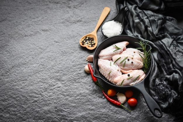 Rauwe kippenvleugels, kruiden en specerijen met peper, chili, tomaat, knoflook, om te koken, rozemarijnkip