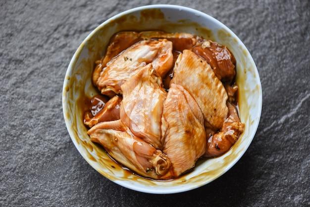 Rauwe kippenvleugels met gemarineerde saus, kruiden en specerijen voor grill of gebakken