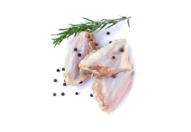 Rauwe kippenvleugels met knoflook, peper en rozemarijn geïsoleerd op een witte achtergrond
