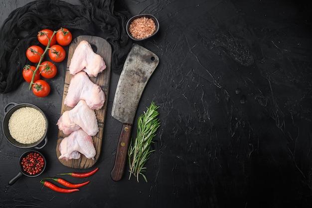 Rauwe kippenvleugels met kruiden set, en oud slagersmes, op zwarte stenen tafel, bovenaanzicht plat lag